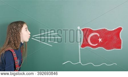 Pre-adolescent Girl Blowing On The School Board Drawn On The Blackboard Turkey Flag. High Resolution
