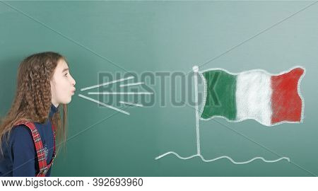 Pre-adolescent Girl Blowing On The School Board Drawn On The Blackboard Italy Flag. High Resolution