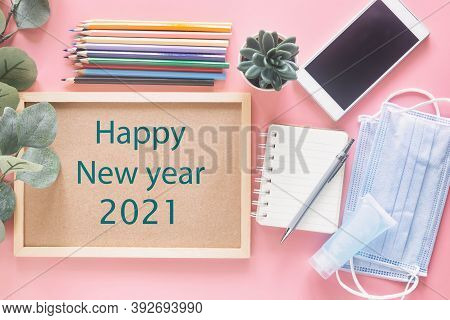 Happy New Year 2021 On Wooden Letter Board With Stationery, Smartphone, Mask And Hand Sanitizer On P