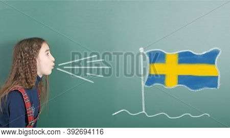 Pre-adolescent Girl Blowing On The School Board Drawn On The Blackboard Sweden Flag. High Resolution