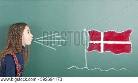 Pre-adolescent Girl Blowing On The School Board Drawn On The Blackboard Denmark Flag. High Resolutio