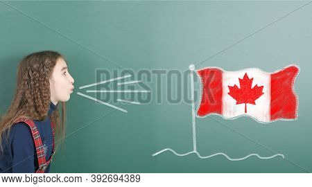 Pre-adolescent Girl Blowing On The School Board Drawn On The Blackboard Canada Flag. High Resolution