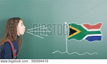 Pre-adolescent Girl Blowing On The School Board Drawn On The Blackboard South Africa Flag. High Reso