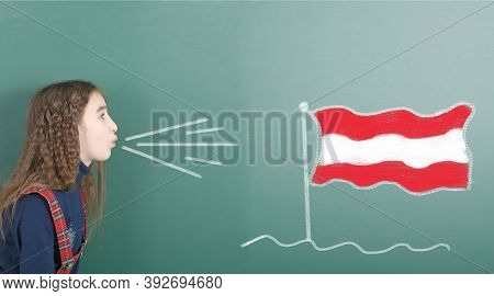 Pre-adolescent Girl Blowing On The School Board Drawn On The Blackboard Austria Flag. High Resolutio