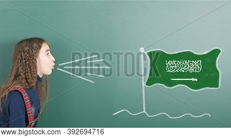 Pre-adolescent Girl Blowing On The School Board Drawn On The Blackboard Saudi Arabia Flag. High Reso
