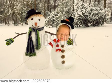Composite image of a newborn baby with a snowman in a winter landscape