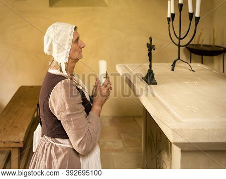 Mature woman in medieval outfit kneeling in prayer in the chapel of a French medieval castle