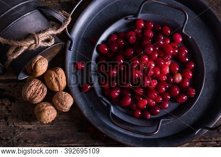 Antique dish and rustic jar filled with fresh cranberries and walnuts for thanksgiving