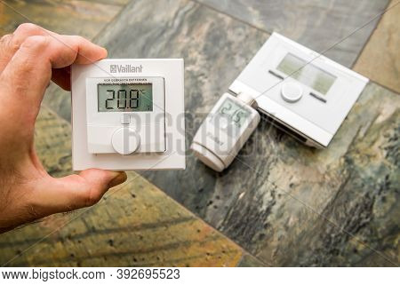 Paris, France - Oct 25, 2020: Pov Man Showing Vaillant Vr51 Room Thermostat With Other Iot Device De