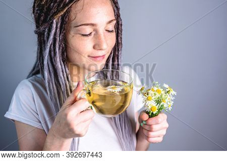 Woman Is Enjoying A Hot Healthy Chamomile Tea. Concept Of Taking A Soothing Herbal Tea After A Diffi
