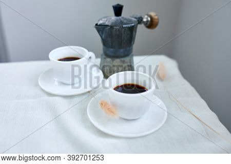 Two Coffee Cups And Italian Coffee Maker Over Table At Home