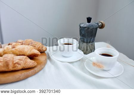 Two Coffee Cups And Italian Coffee Maker With Croissant.
