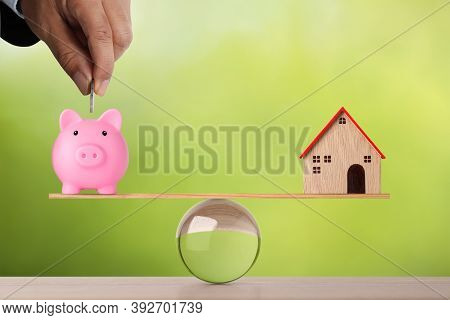 Businessman Hand Putting Coin Into Piggy Bank With Model House On Wooden Marble Seesaw Balancing On