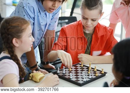 Cute And Smart Kids Playing Chess In Class (education Concept)