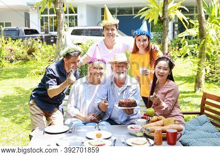 Happy Multiethnic Family Giving Surprise Gift Homemade Baked Cake To Caucasian Grandfather On His Ha