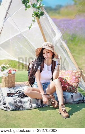 Asian Beautiful Woman, Long Hair In White Shirt With Camera And Hat Sitting On Verbena Filed With Bl