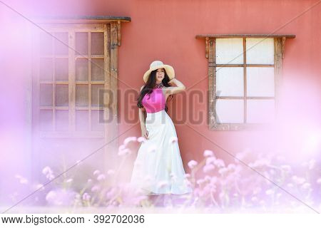 Asian Beautiful Woman, Long Hair In Cute Dress On Verbena Filed In Winter With Blue Sky. Beautiful C
