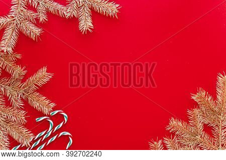 Red Christmas Or New Year Background, Simple Composition Of Golden Fir Branches And Christmas Toys,
