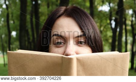 Portrait Of A Young Woman With An Open Untitled Book Held Close To Her Face. Brunette Covering Half
