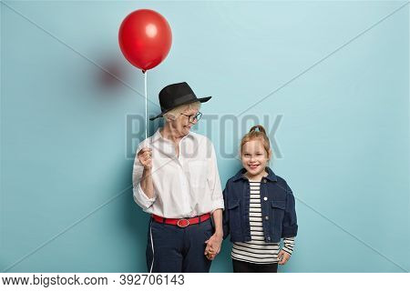 Half Length Shot Of Affectionate Grandma Congratulates Little Kid With First Day At School, Holds Re