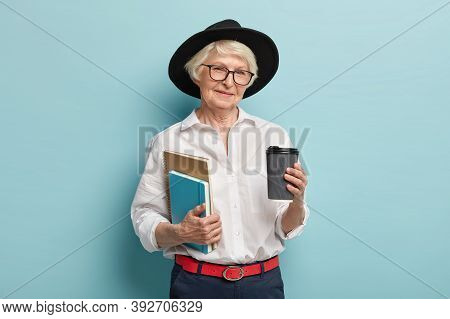 Studying In Old Age. Pleased Wrinkled Woman In Black Headgear, Holds Two Notepads, Takeaway Coffee,