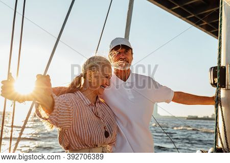 Elderly Couple Enjoying Their Vacation On A Private Yacht. Two Senior People Standing Together On A