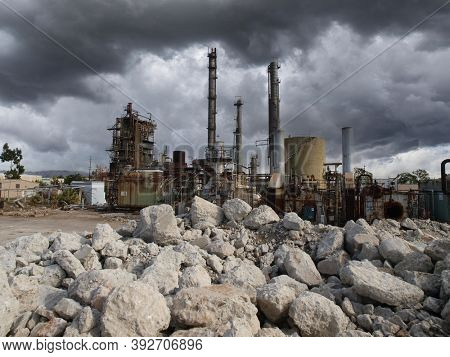 Rubble and rust at closed oil and petrochemical industrial refinery with stormy sky.