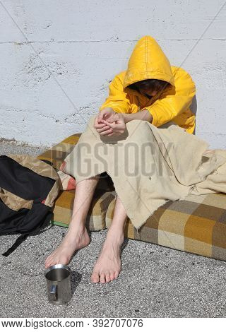 Poor Barefoot Homeless Man In A Yellow Hood Asks For Charity From Passersby In The Metropolis