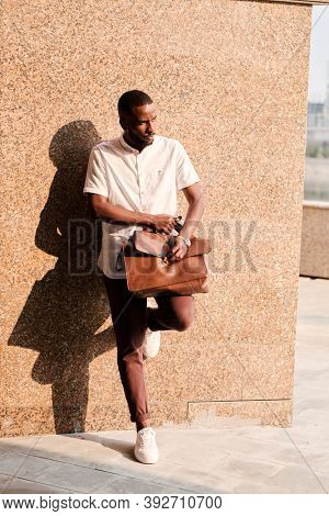 Young African businessman or agent in smart casualwear holding brown leather handbag on his knee while leaning against wall of building