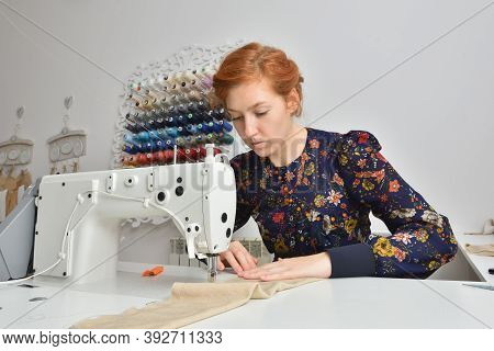 Young Woman Working On A Sewing Machine In A Sewing Studio