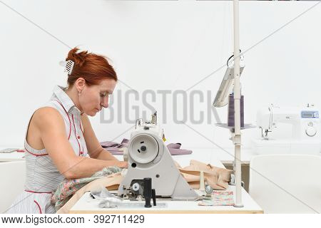 Middle Aged Woman Works At A Sewing Machine In A Sewing Workshop