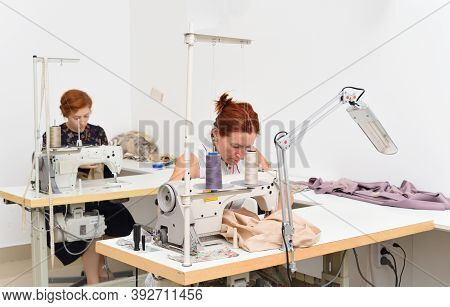 Two Caucasian Women Seamstress At Work On Sewing Machines In A Sewing Studio