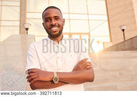 Young African businessman with toothy smile standing in front of camera with his arms crossed by chest in urban environment on sunny day