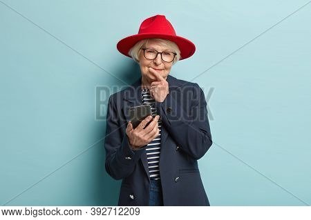 Wise Thoughtful Pleased Elderly Wrinkled Woman Holds Chin, Reads Notification, Connected To Wireless
