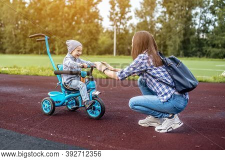 Happy Toddler Boy Is Successfully Going To His Mother On A Childrens Tricycle. Concept Of Learning T