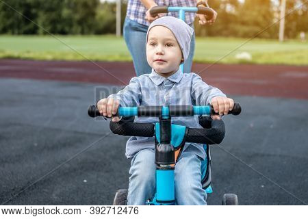 Young Mother Is Pushing A Childs Tricycle With A Toddler Boy On A Walk. Concept Of Learning To Ride