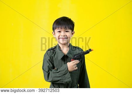 Boy Wearing A Military Uniform With A Gun, On Yellow Backdrop.