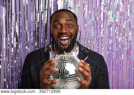 Happy Plump Dark Skinned Man With Toothy Glad Smile, Holds Disco Ball, Has Stag Party, Comes On Disc