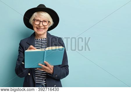Portrait Of Pleased Female Pensioner Writes Plan Strategy In Diary, Has Nice Clever Look, Wears Glas