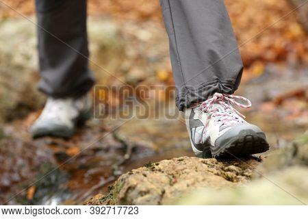 Close Up Of A Trekker Legs Wearing Trekking Boots Crossing A Creek In Autumn In A Forest