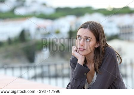 Worried Woman Thinking Looking At Side From A Balcony In A Beach Town On Vacation
