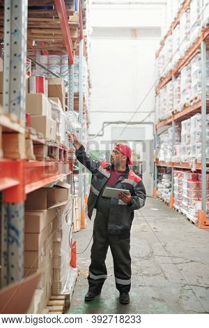 Mixed-race worker of warehouse in uniform scanning qr codes on big boxes while standing in aisle by huge shelf with packed goods