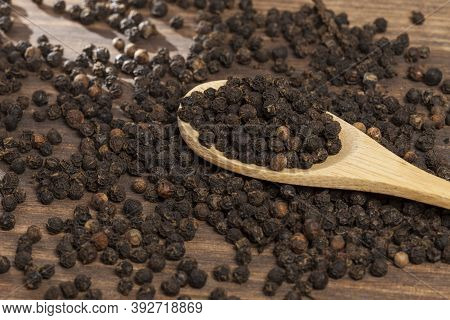 Piper Nigrum - Black Peppercorns; Photo On Dark Wooden Background.