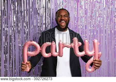 Young Black Man Dances On Disco, Holds Letter Shaped Balloons, Stands Against Party Background, Wear