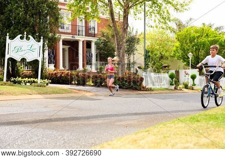Kids And Joggers On Street Of Wealthy Gated Community Neighborhood