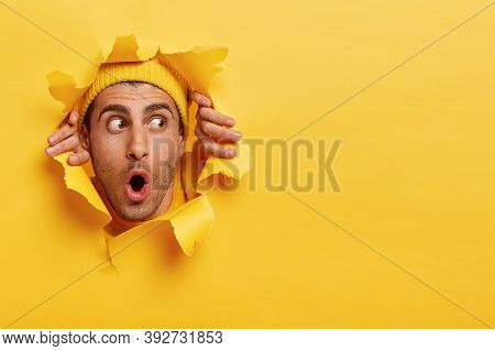 Surprised Male Face Through Paper Hole. Emotional Astonished Young Man Wears Yellow Headgear, Makes