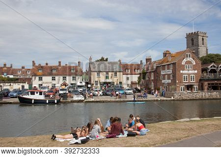 People Sat By The River Frome In The Summer In Wareham, Dorset In The Uk, Taken On The 23rd July 202