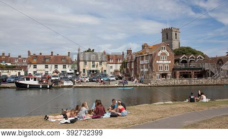 Teenagers Sat By The River Frome In Wareham, Dorset In The Uk, Taken On The 23rd July 2020
