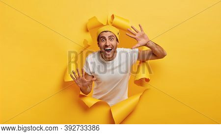 Cheerful Optimistic Unshaven Young Man Shows Palms, Feels Happy And Delighted, Wears Fashionable Clo