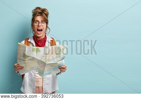 Photo Of Frustrated Woman Traveler Lost In City, Looks Depressed At Paper Map, Shouts From Despair,